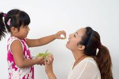 Mother daughter eat fruit Royalty Free Stock Image