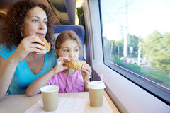 Mother and daughter eat near window of train Stock Photos