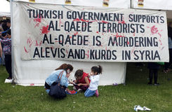 Mother and daughter eat watermelon. Mother and her daughters eat watermelon in front of the banner with political slogan during the he Alawite Park Festival in Stock Images