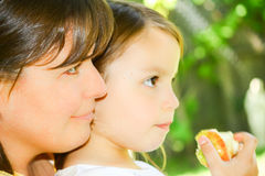 Mother With Daughter Eating Apple Stock Photos