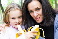 Mother and daughter eating banana Stock Photography