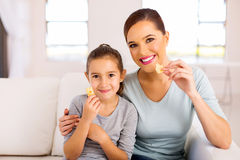 mother daughter eating biscuits Stock Image