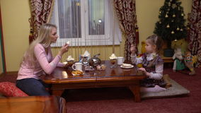 Mother and daughter eating biscuits in a cafe. Christmas tree inside stock video
