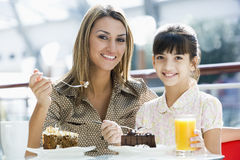 Mother and daughter eating cake in cafe Stock Images