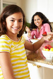 Mother and daughter eating cereal and fruit Stock Photo