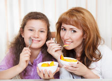 Mother and daughter eating cereal and fruit Stock Photography