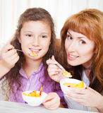 Mother and daughter eating cereal and fruit Royalty Free Stock Image