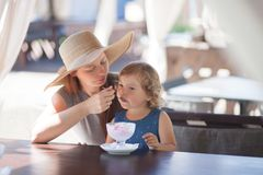 Mother and daughter eating ice cream at the restaurant. Royalty Free Stock Image