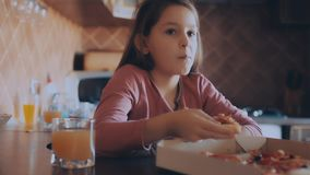 Mother and daughter eating pizza in the kitchen. Young mother and her little daughter eating pizza and having fun stock footage