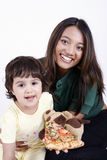 Mother and daughter eating pizza slice stock images