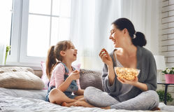 Mother and daughter eating popcorn. Happy loving family. Mother and her daughter child girl are eating popcorn on the bed in the room Royalty Free Stock Photos