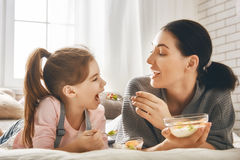 Mother and daughter eating salad Stock Photos