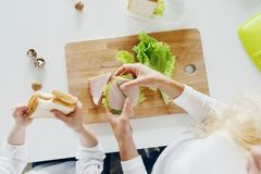 Mother daughter eating sandwiches home kitchen top view stock photo