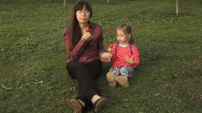 Mother and daughter eating strawberries on a picnic sitting on green grass. Mother and daughter eating strawberries sitting on the grass in a public park. A stock video