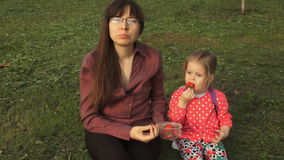 Mother and daughter eating strawberries on a picnic sitting on green grass. A young businesswoman and her baby daughter are eating a ripe strawberry. A little stock video footage