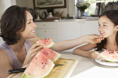Mother And Daughter Eating Watermelon At Table Stock Photos