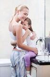 Mother and daughter embrace each other in bathroom Stock Photography