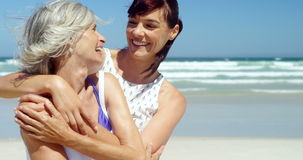 Mother and daughter embracing each other at beach stock footage