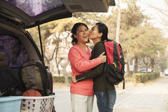 Mother and daughter embracing and giving a kiss behind car on college campus royalty free stock photography