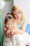 Mother and daughter embracing indoors Royalty Free Stock Images