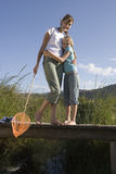 Mother and daughter (7-9) embracing on small wooden footbridge above stream, woman with fishing net, smiling, portrait Royalty Free Stock Images
