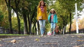 Mother and daughter on empty autumn alley. Mother and daughter on an empty autumn alley stock video