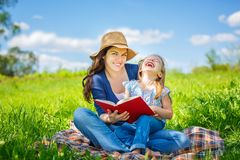 Mother and daughter reading book on green summer meadow. Mother and daughter enjoy reading book sitting on green meadow in the summer park royalty free stock images
