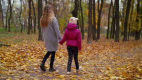 Mother and daughter enjoying colorful autumn nature. Positive healthy lifestyle mother and elementary age daughter enjoying beautiful autumn nature during a walk stock video