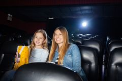 Mother And Daughter Enjoying Film In Theater Stock Image