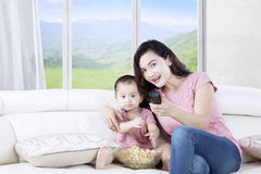 Mother with daughter enjoying movie at home Royalty Free Stock Photos