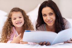 Mother and daughter enjoying reading together Royalty Free Stock Photos