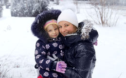 Mother and daughter enjoying snow in winter Stock Image