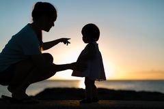 Mother and daughter enjoying the sunset together. Silhouette style. Sunset / sunrise, Young women and 1 yo toddler Stock Photography