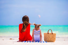 Mother and daughter enjoying time at tropical beach. Happy family with straw bag on summer holidays Stock Image