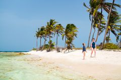 Mother and daughter at beach. Mother and daughter enjoying tropical beach vacation stock image