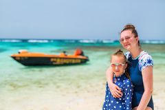 Mother and daughter at beach. Mother and daughter enjoying tropical beach vacation royalty free stock photo
