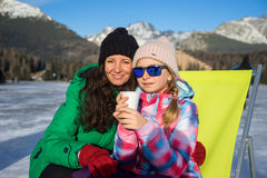 Mother and daughter enjoying winter vacations. In the mountains. Posing with a cup of hot tea in a sunny day. Girl sitting in sunbed Stock Photos