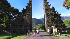 Mother and daughter entering traditional Balinese gate stock footage