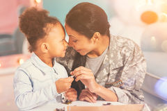 Mother and daughter Eskimo-kissing while doing a puzzle Stock Photos