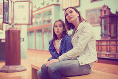 Mother and daughter exploring expositions. Beautiful mother and daughter exploring expositions of previous centuries in museum royalty free stock images