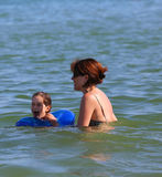 Mother and daughter with failsafe playing in the sea Stock Images