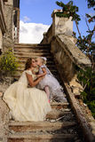 Mother and daughter. Fairy and angel on the stairs next to the abandoned house Stock Photo