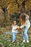 Mother and daughter of fallen leaves. Autumn. Royalty Free Stock Image