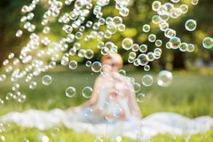 Mother and daughter family time, blowing soap-bubbles Stock Photos