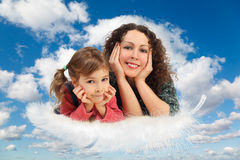 Mother with daughter on feather on clouds Stock Photo