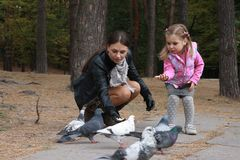 Mother and daughter feed birds in the park Royalty Free Stock Photo