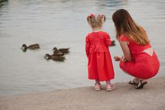 Mother with daughter feeding ducks in park. Mother with daughter feeding ducks in summer park royalty free stock photography
