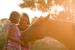 Mother and daughter feeding her handsome horse Stock Images