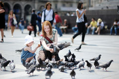 Mother and daughter feeding pigeons Royalty Free Stock Image