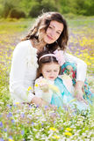 Mother and daughter in field with colorful flowers Stock Image